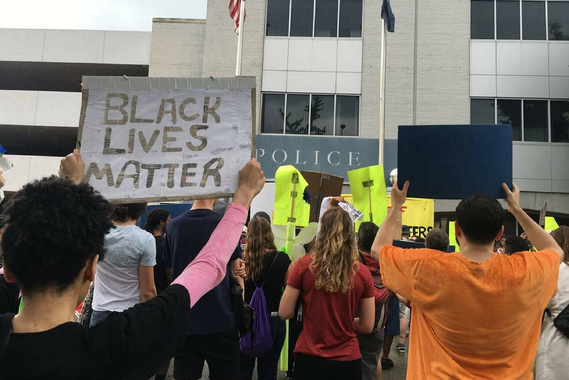 "Stephanie Younger, back to the viewer, held a sign that said ""Black Lives Matter"" while she joined many other protesters in front of Richmond Police headquarter"