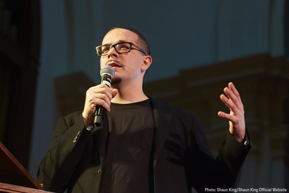 picture of Shaun King speaking at a public event. He dressed in black against a black background.
