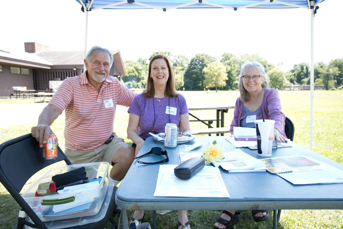 picture of three people at an outside table at Crabfest, helping out with registration