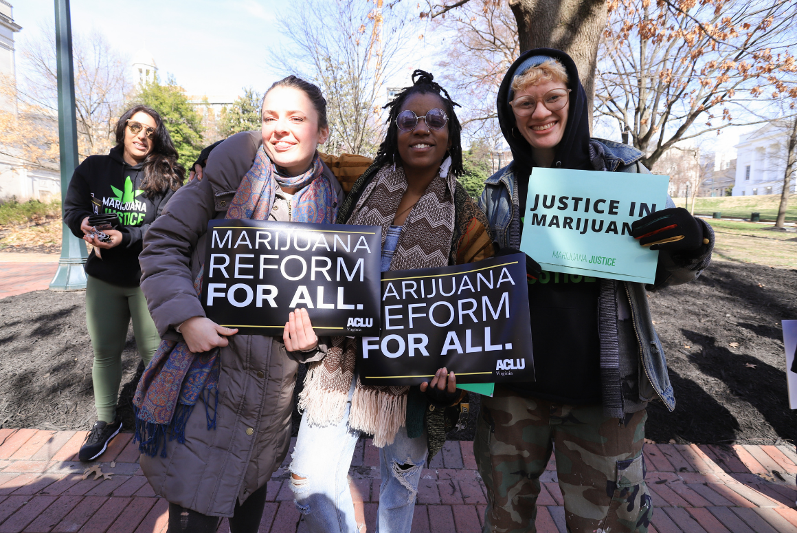 "Three advocates holding signs that say ""marijuana reform for all"" and ""justice in marijuana"""