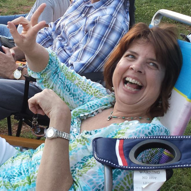 photo of Gay Ellen Plack, a white middle-aged woman, sitting on a lawn chair, laughing heartily.