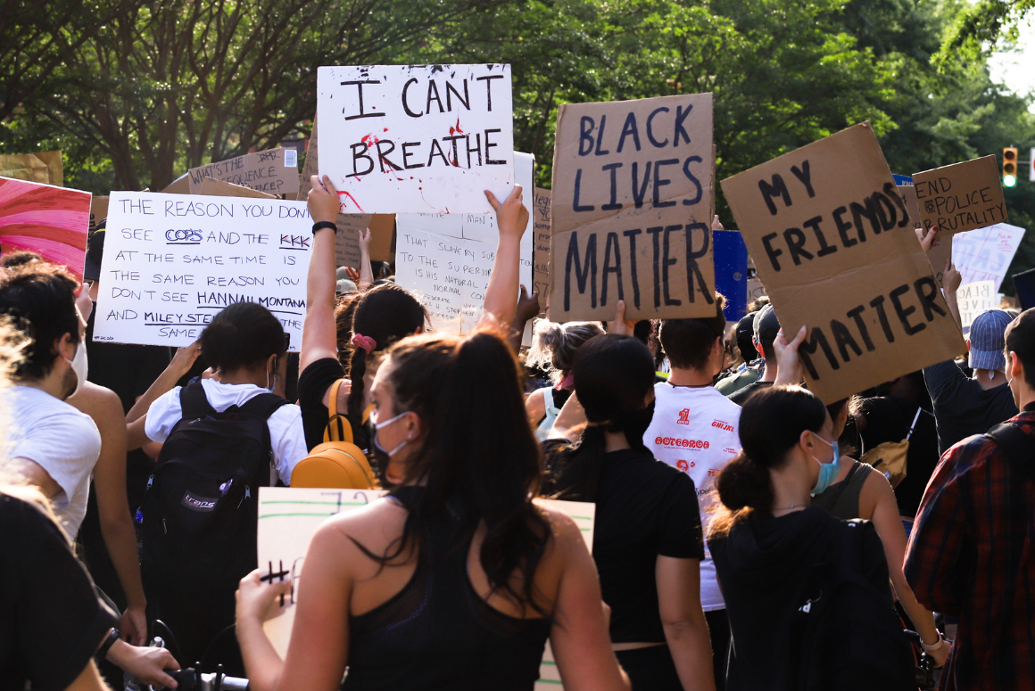 protesters with their backs against the camera, holding signs with messages supporting Black Lives Matter