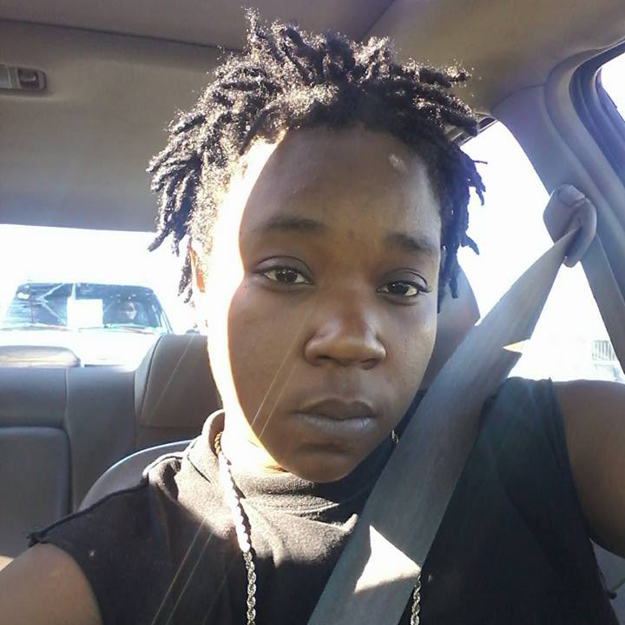 photo of India Beaty, a Black woman with short hair in locks. Photo was taken in her car.
