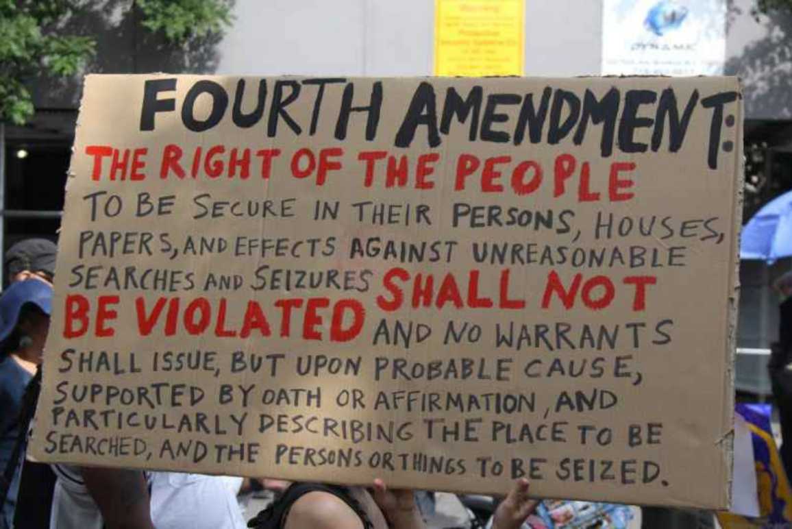 a protest sign with the fourth amendment written out on it