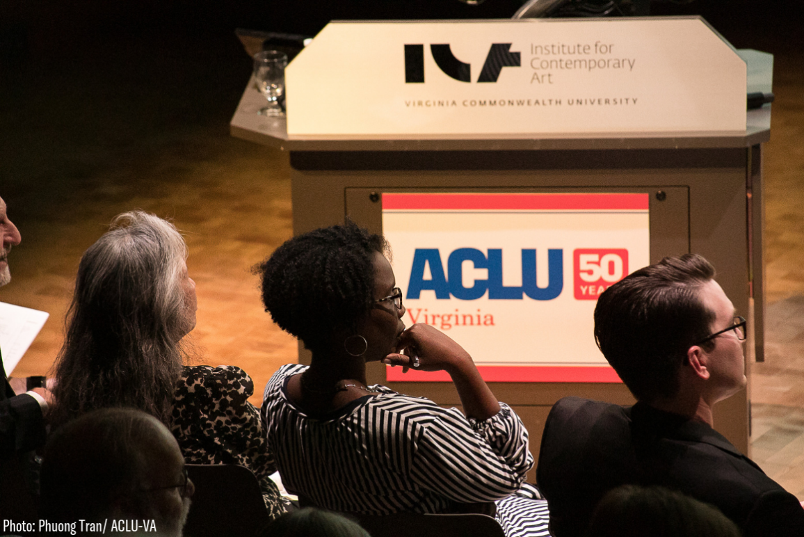Photo of our board member and author of this piece from behind, a Black woman wearing glasses in a black-and-white-stripe dress, against a podium with the ACLU-VA logo