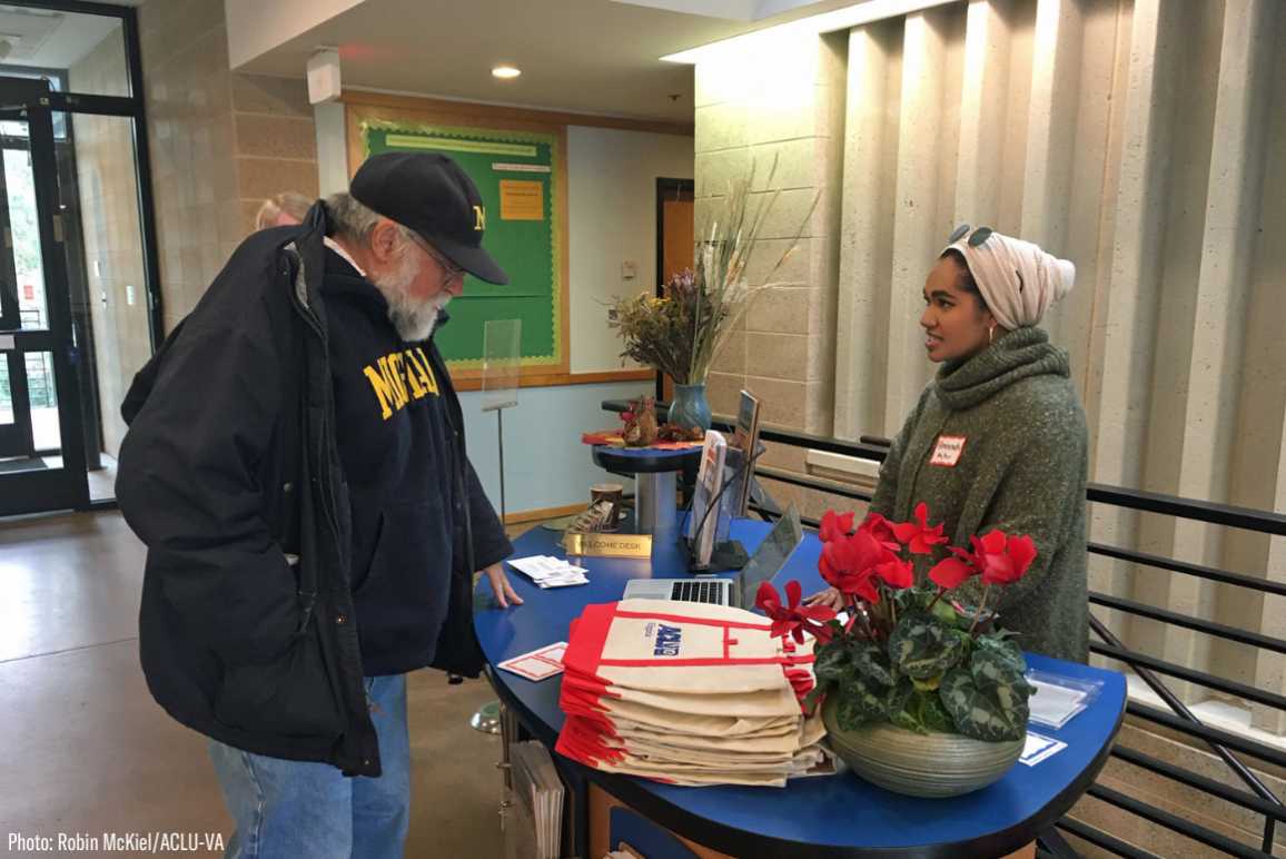 Our intern Ameenah in her hijab at the reception table greeting guests at our 2020 Legislative forum