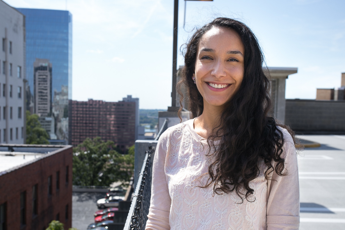 bio pic of our Office Assistant Anjali Carroll, a young woman of Indian descent with long curly hair against a background of buildings in the Richmond area