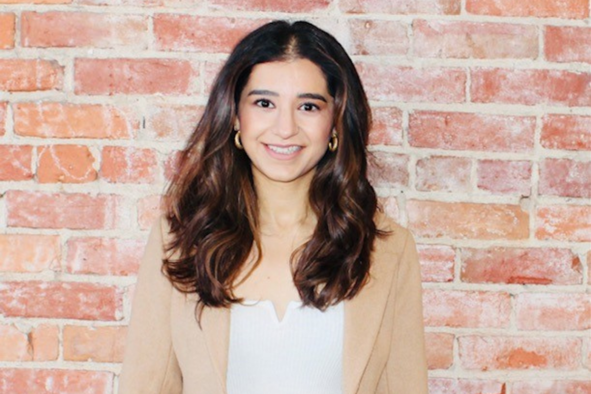 photo of Ashna Khanna, an indian-descent American with long dark brown hair, oval face, bright eyes, leaning against a red brick wall