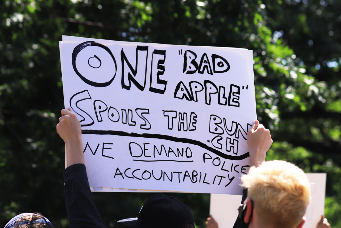 "protester hold a sign on white paper with black lettering: ""one bad apple spoils the bunch. We demand police accountability."""