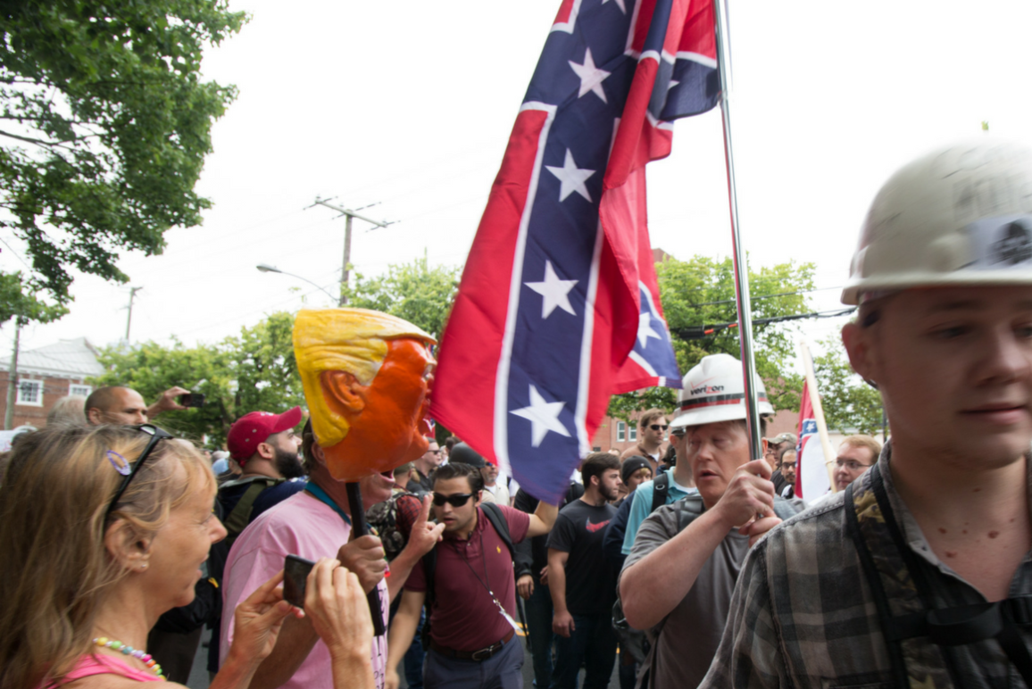 Protester holding Confederate flag and counter protester holding mocking Trump head on a stick at the Aug. 12 Unite the Right protest in Charlottesville