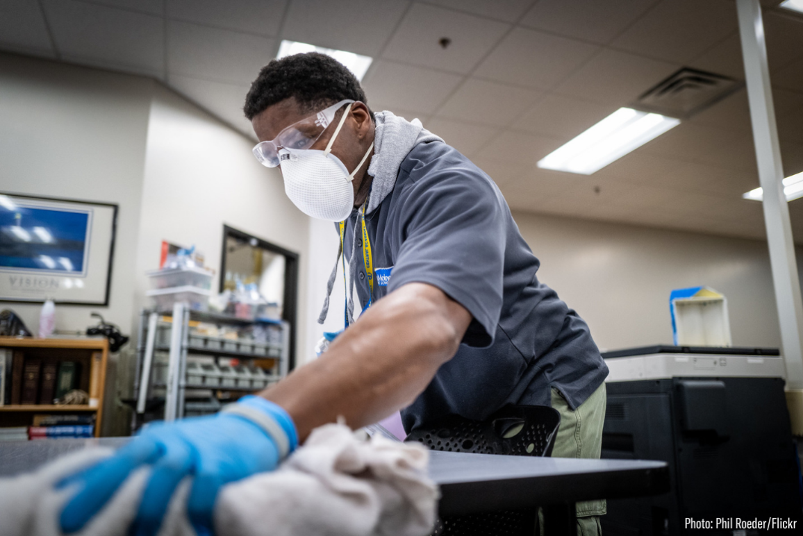 a Black man wearing a mask and cleaning a table during the COVID-19 pandemic