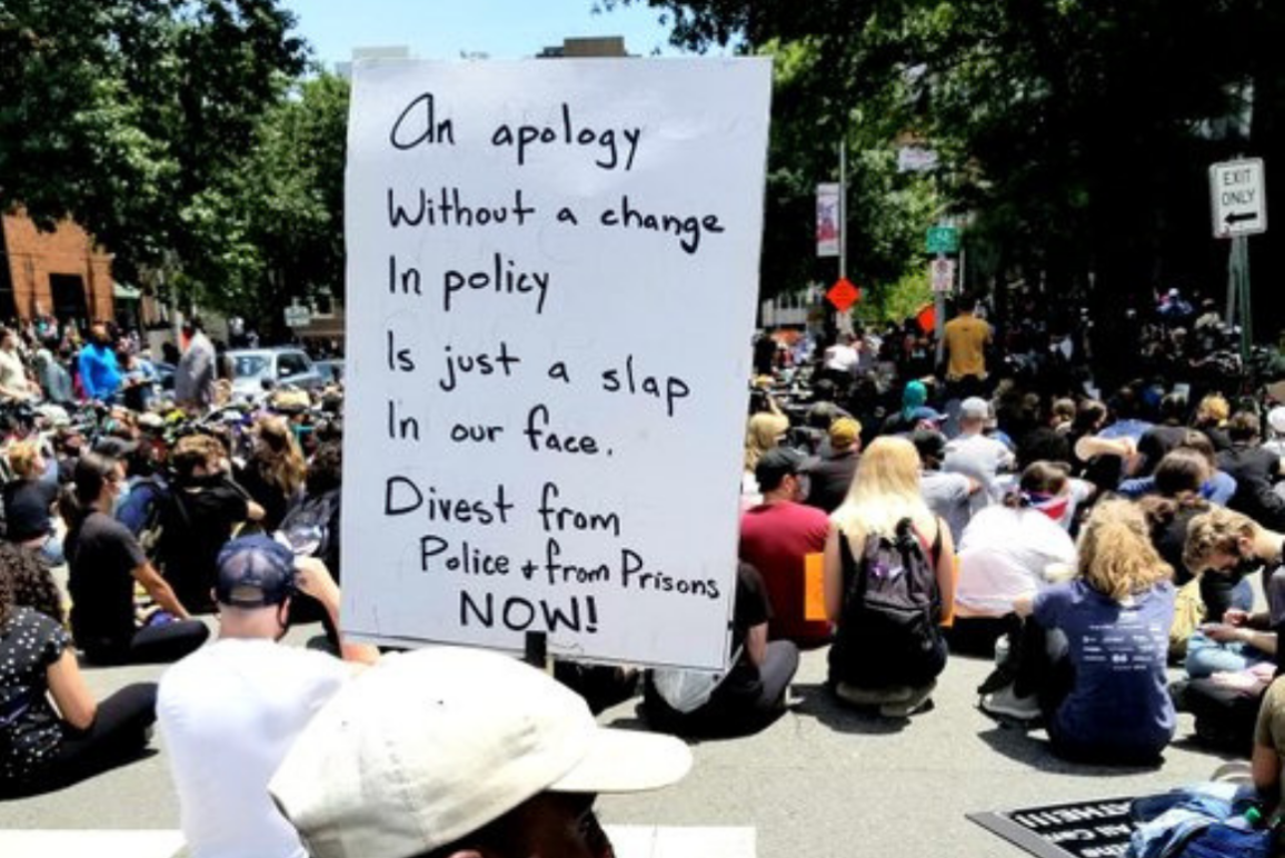 """a Black protester holding a sign that says """"an apology without a change in policy is just a slap in our face, Divest from policing + prison now"""""""