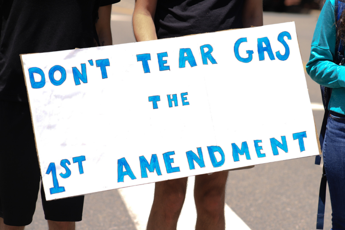 "a white sign with blue text that says ""don't tear gas the first amendment"""