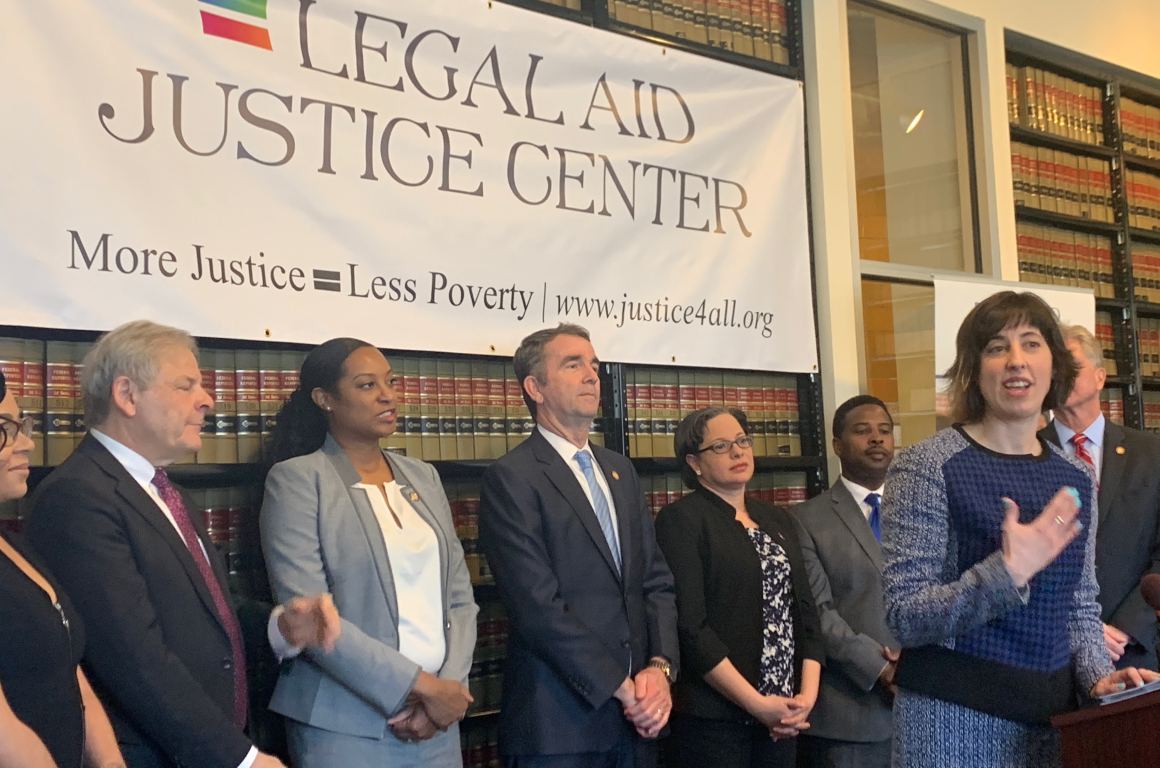 press conference at the legal aid justice center's office in Charlottesville, with the governor  and lawmakers in the back listening to LAJC Executive director at the podium