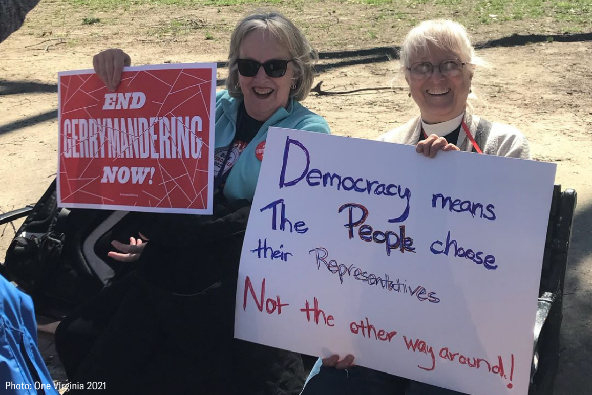 "two protesters holding signs that say ""End gerrymandering now"" and ""Democracy means the people choose their reps, not the other way around"""