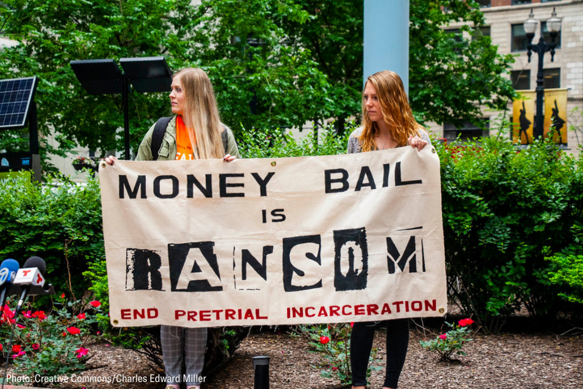 "two woman holding a banner that said ""money bail is ransom. End pretrial incarceration."""