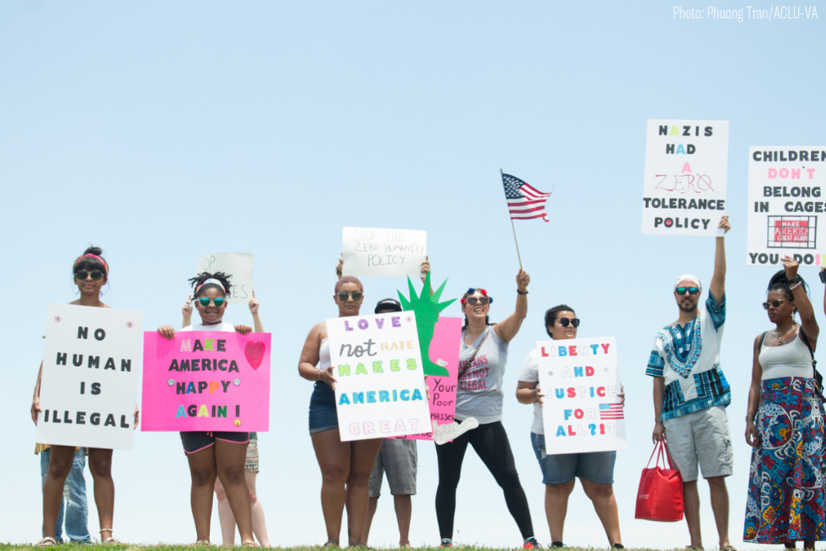 "A row of protesters holding signs with messages supportive of immigrants (""No Body is Illegal"" ""Make America Happy Again"" ""Love Not Hate Makes America Great"" etc)"
