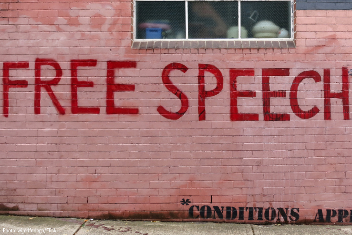 "red graffiti on pink wall that says ""Free Speech"""