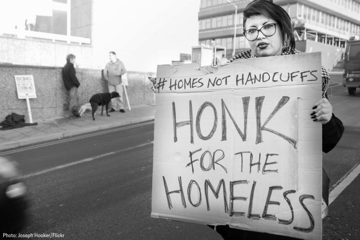 "black and white picture of a woman holding a sign that says ""Homes Not Handcuffs: Honk for the homeless."""
