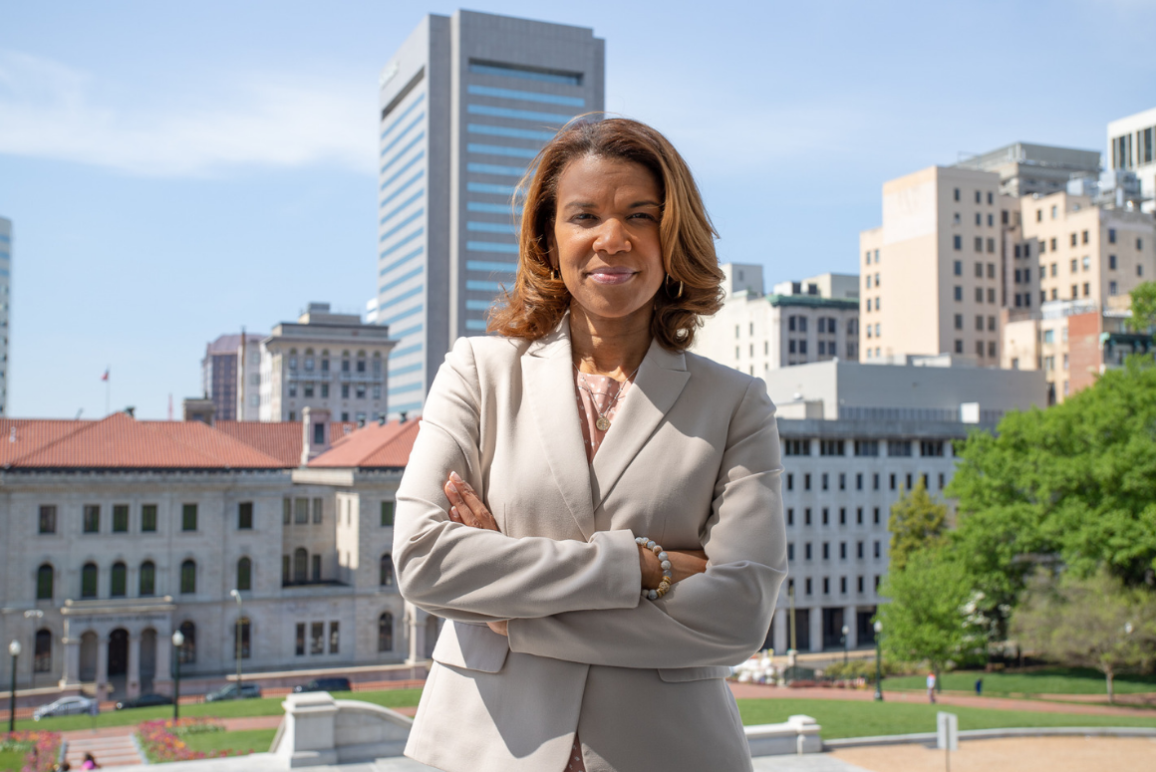 A picture of our Campaign Director Kemba Smith Pradia, a confident, strong-willed black woman standing with her arms folded in front of her chest, with buildings and courthouses in the background.