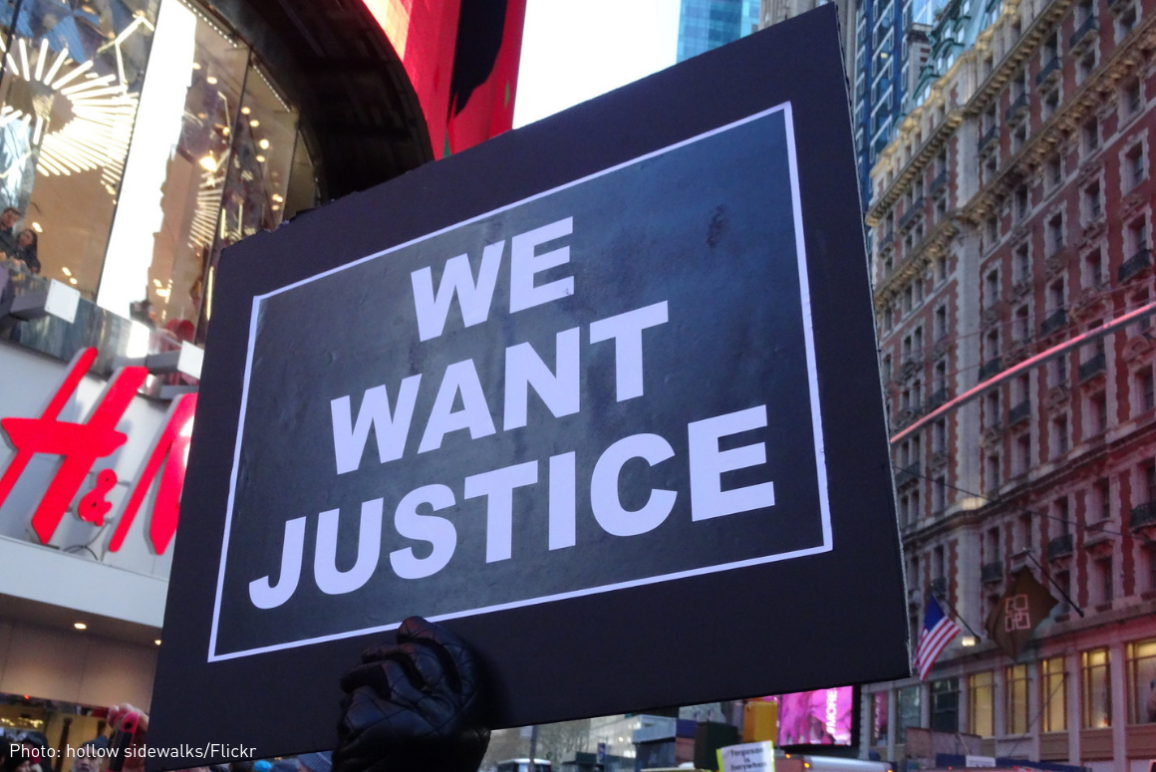 "a protest sign that says ""We Want Justice"""