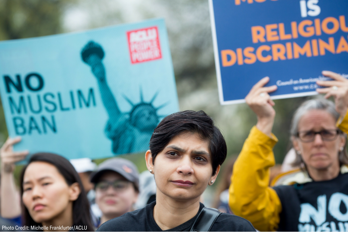 "Photo of a protest against the Muslim Ban, with a Muslim woman in the foreground and an ACLU poster that said ""No Muslim Ban"" in the background"
