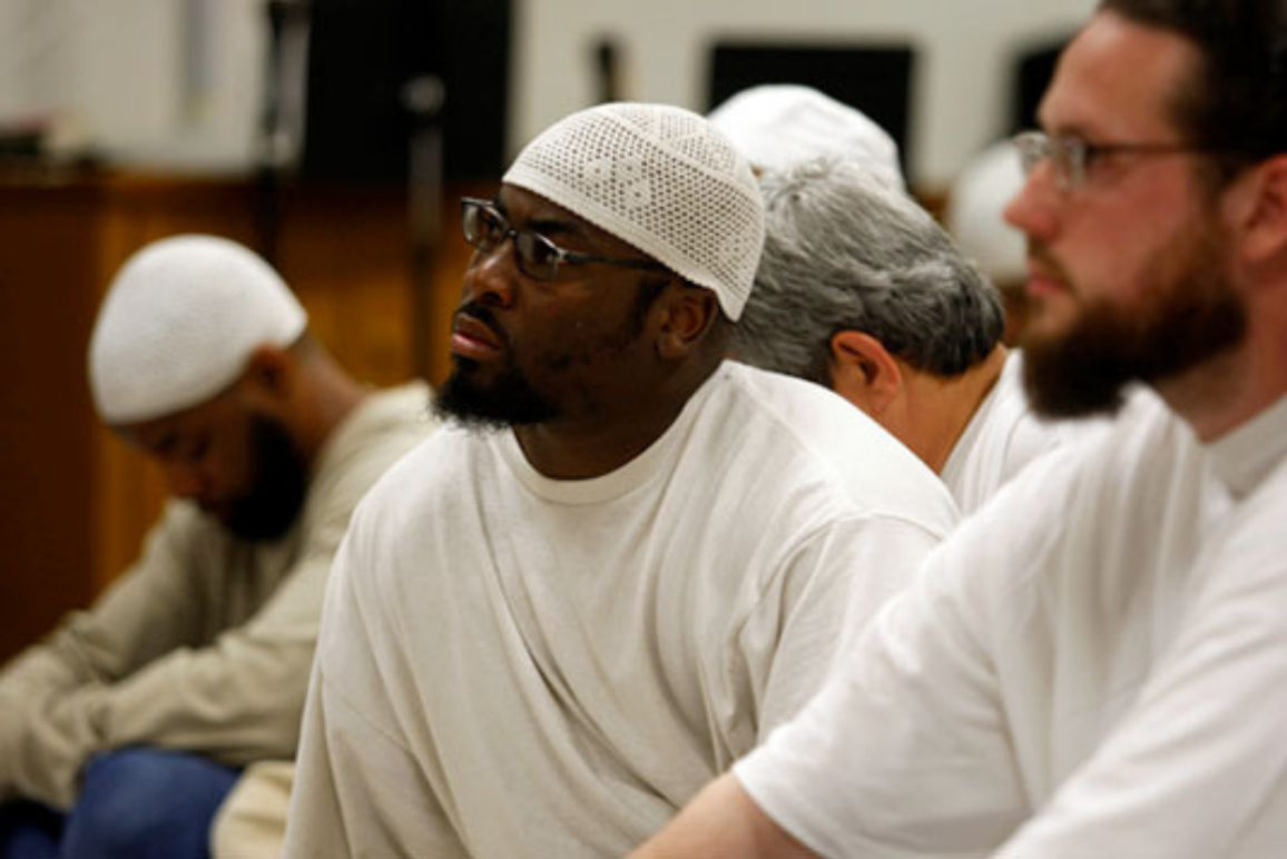 A Black Muslim inmate wearing a white cap (taqiya). He was looking up, as if he was listening to someone.