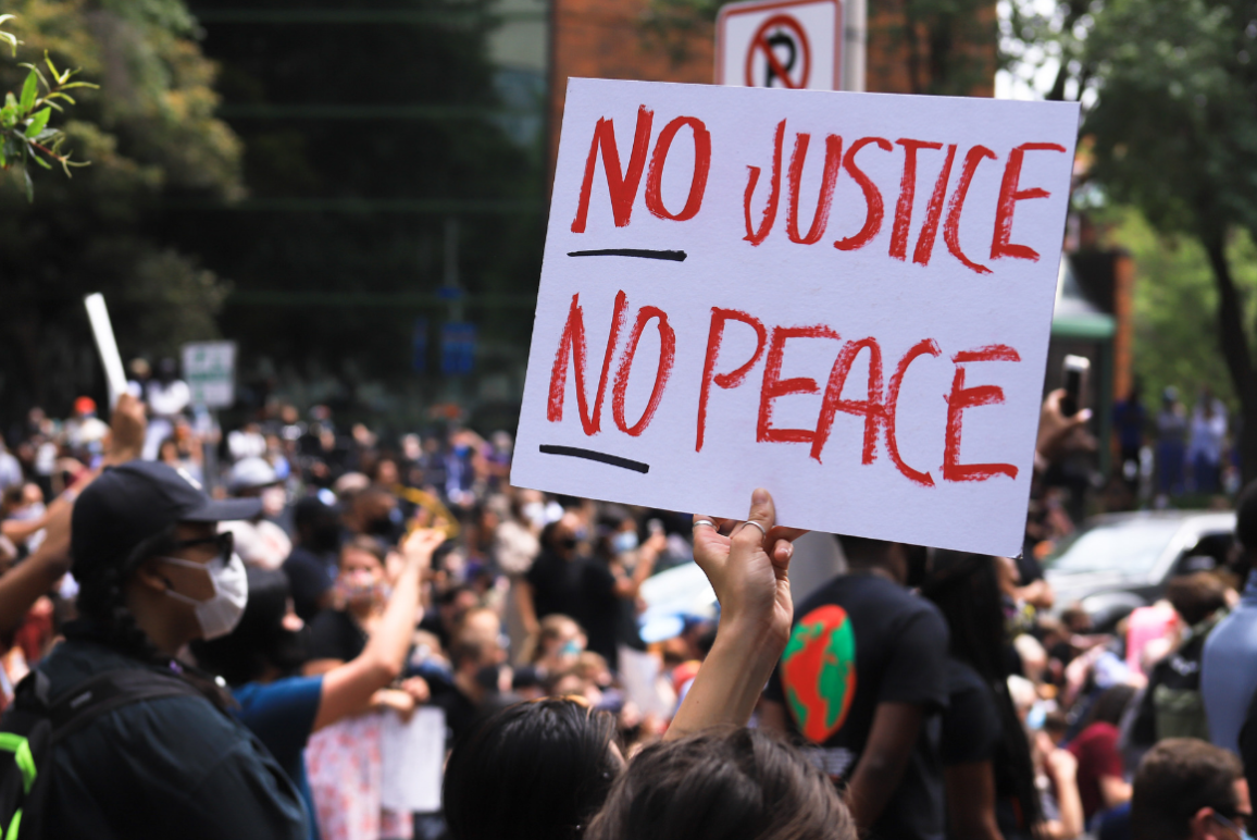 "a white protest sign with the text in red ""No Justice No Peace"""