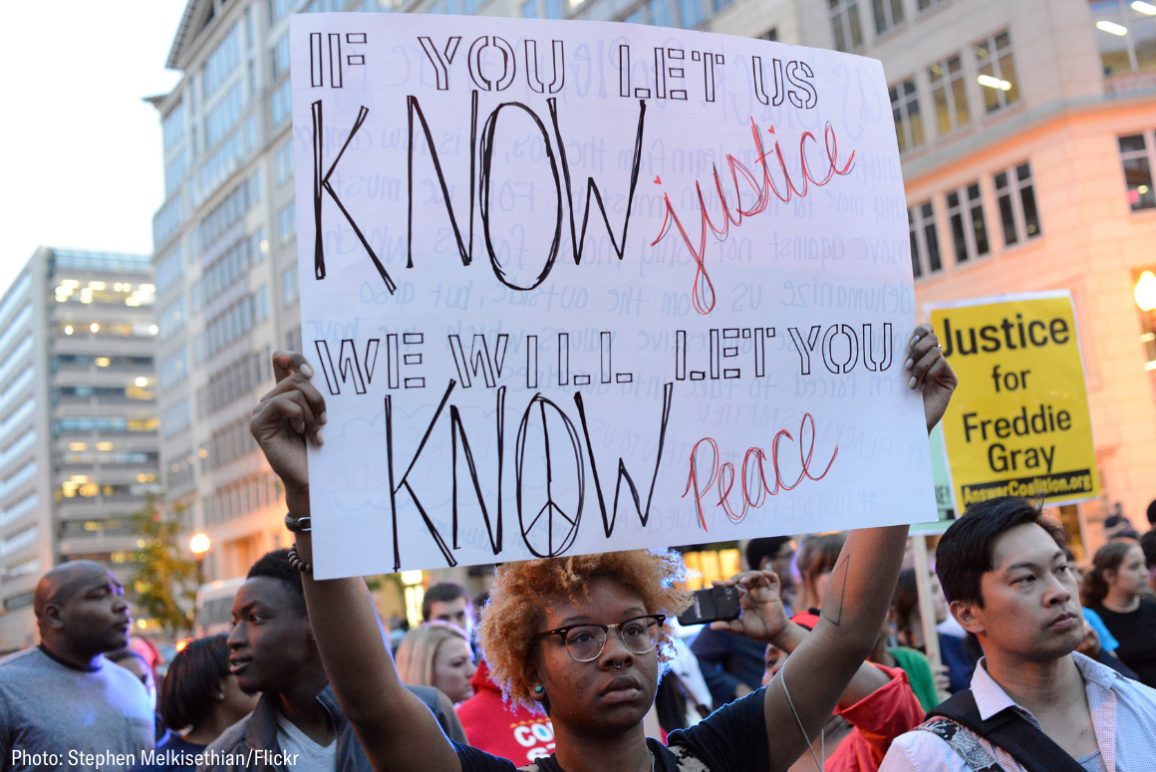 "a Black protester holding a sign that says ""if you let us know justice, we will let you know peace"""