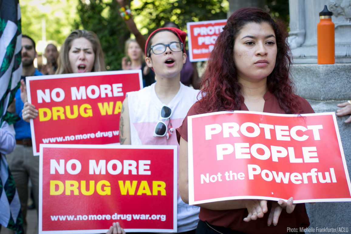 """protesters holding signs that say """"no more drug war"""" and """"protect people not the powerful"""""""