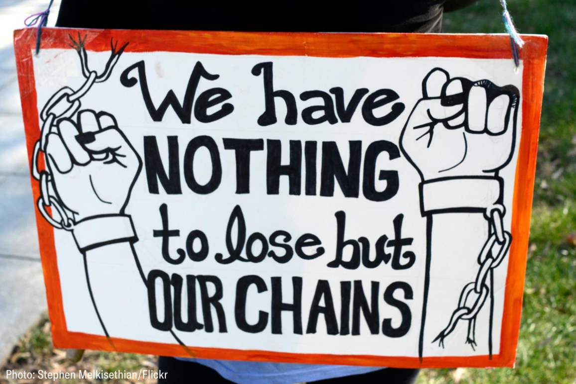 "a white sign with red frame with two arms breaking away from a chain, text reads ""we have nothing to lose but our chains"""