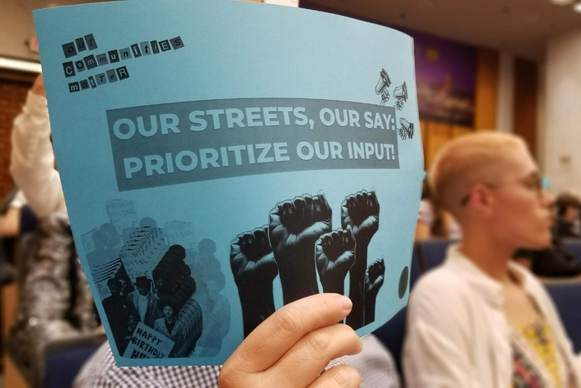 """blue sign with text that says """"our streets, our say: prioritize our input."""""""