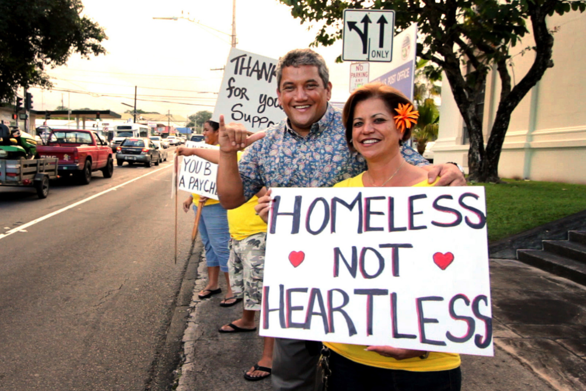 """A woman holding a sign that says """"Homeless not Heartless"""""""