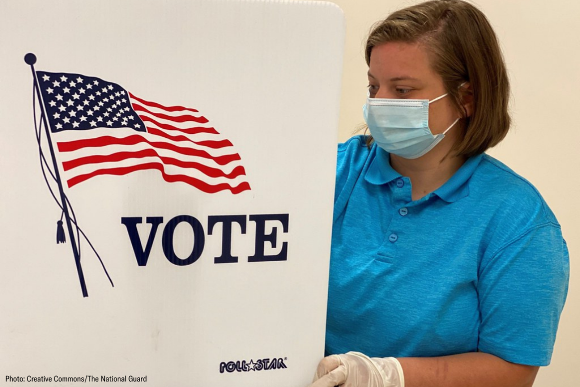 a poll worker cleaned up a polling station while wearing mask and gloves
