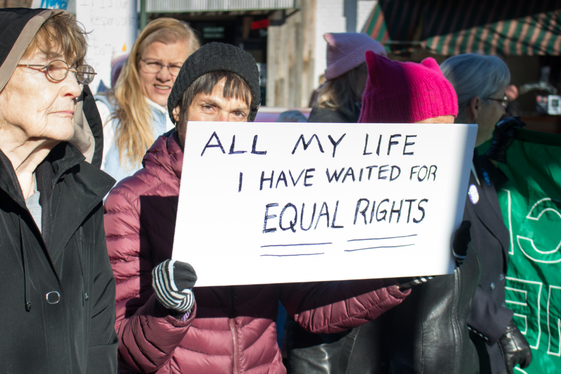 "A woman holding a sign that said ""All my Life I have waited for equal rights"" at the Women's March in Richmond"