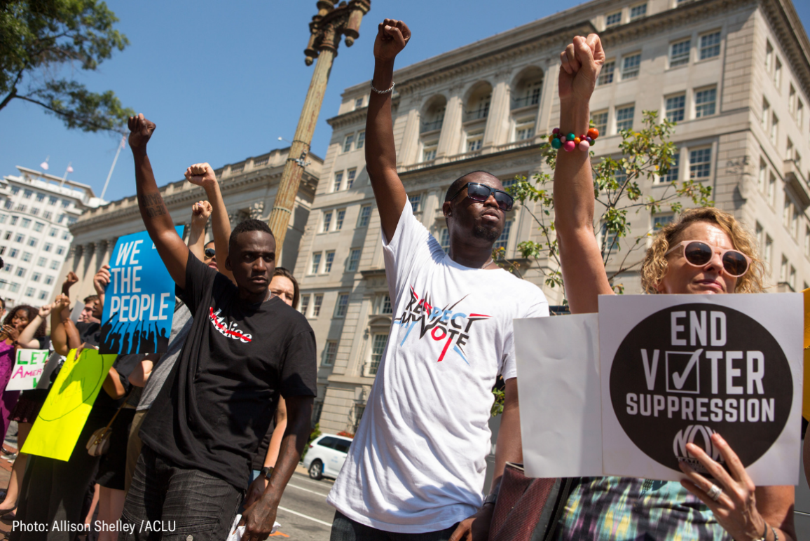 """protesters holding signs that say """"End Voter Suppression"""" and """"Respect my Vote"""""""