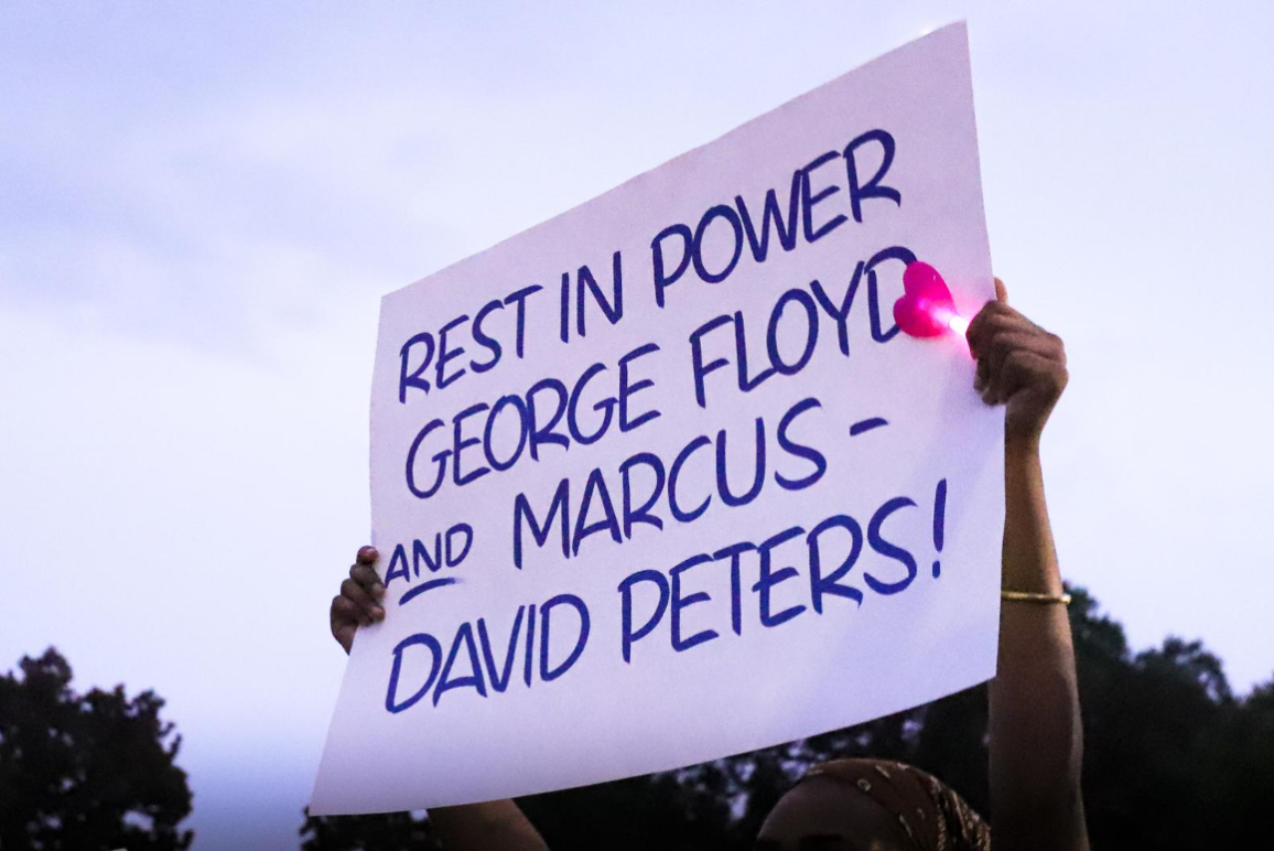 "a black woman holding a sign that says ""rest in power George Floyd and Marcus-David Peters"""