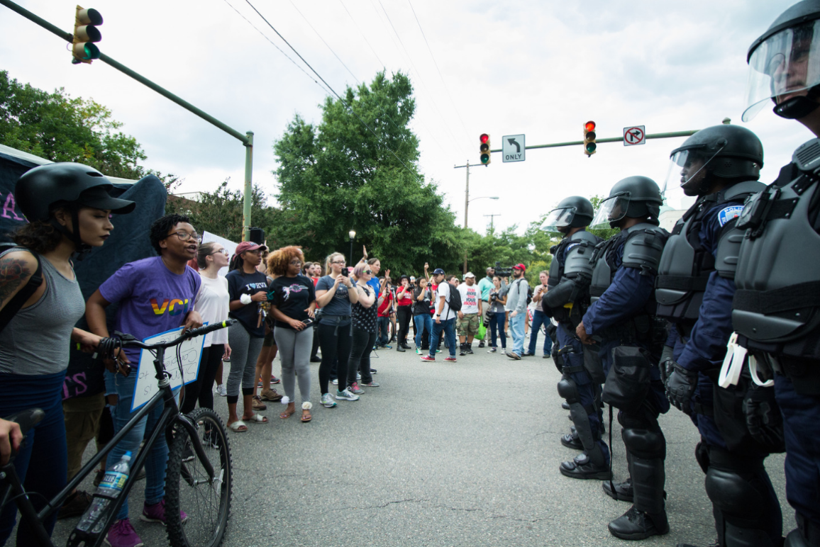 Richmond police officers in SWAT uniform against a group of protesters near VCU campus.