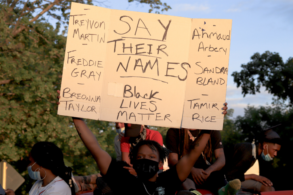 "a sign saying ""say their names"" with the name of Breonna Taylor, Tamir Rice, and so many more"