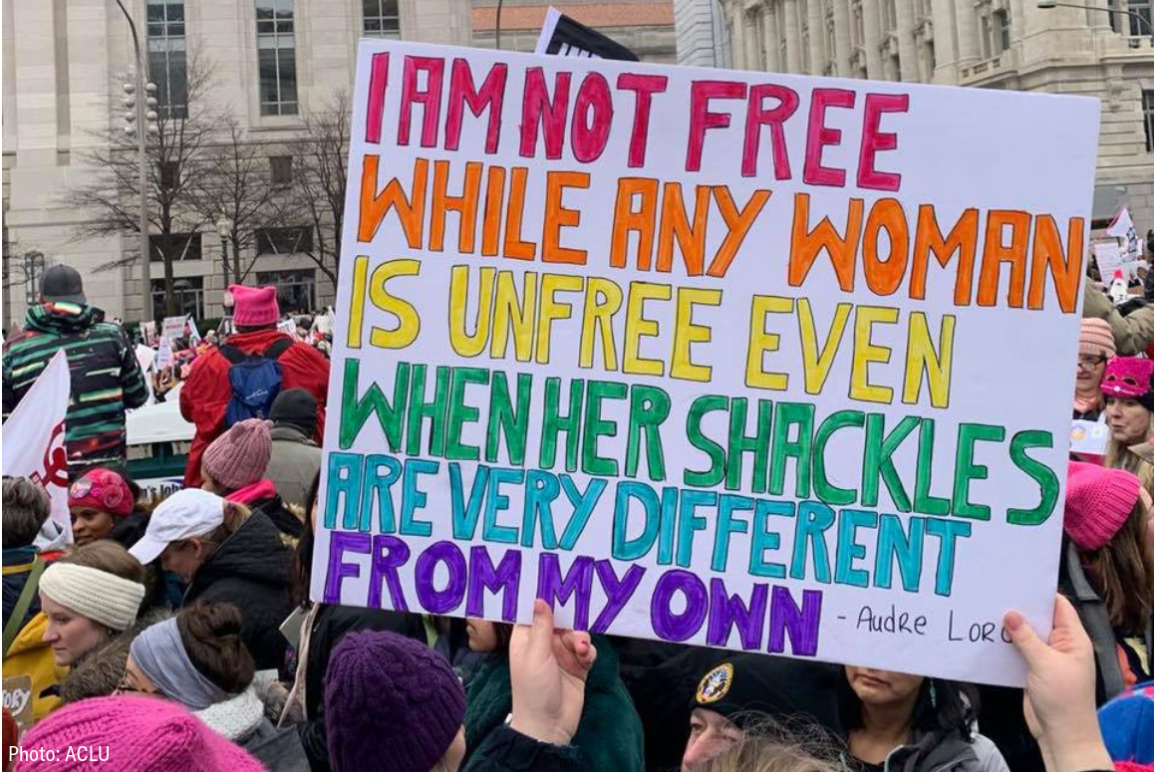 """A sign with a quote from Audre Lorde """"I am not free while any woman is unfree even when her shackles are very different from my own"""""""