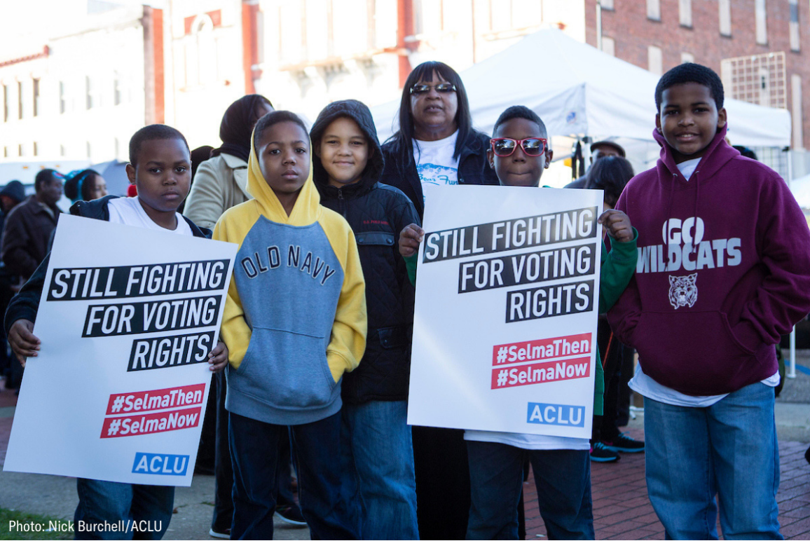 "A group of black youths holding signs that say ""still fighting for voting rights"""