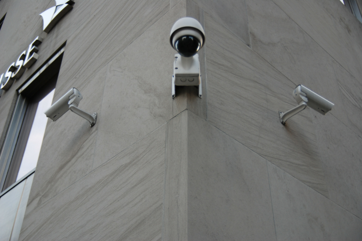 Three surveillance cameras attached to a building