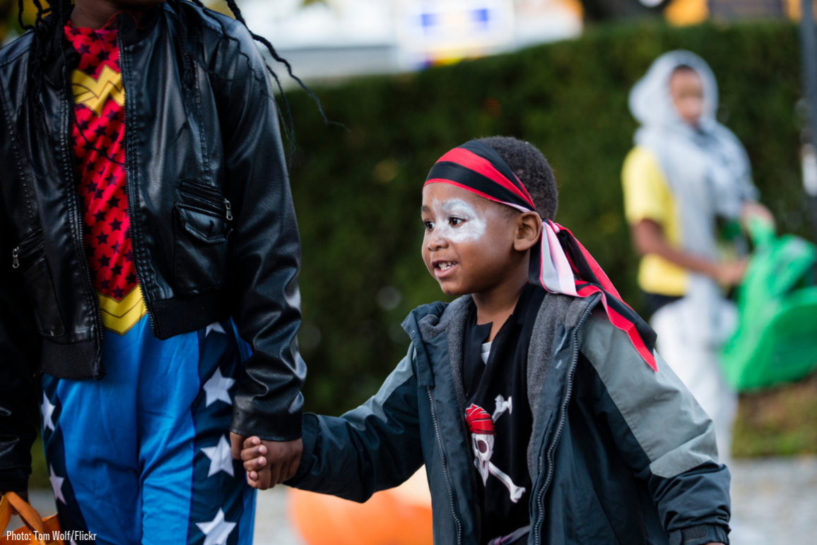 A black kid dressing in pirate clothing went trick or treating with an older kid
