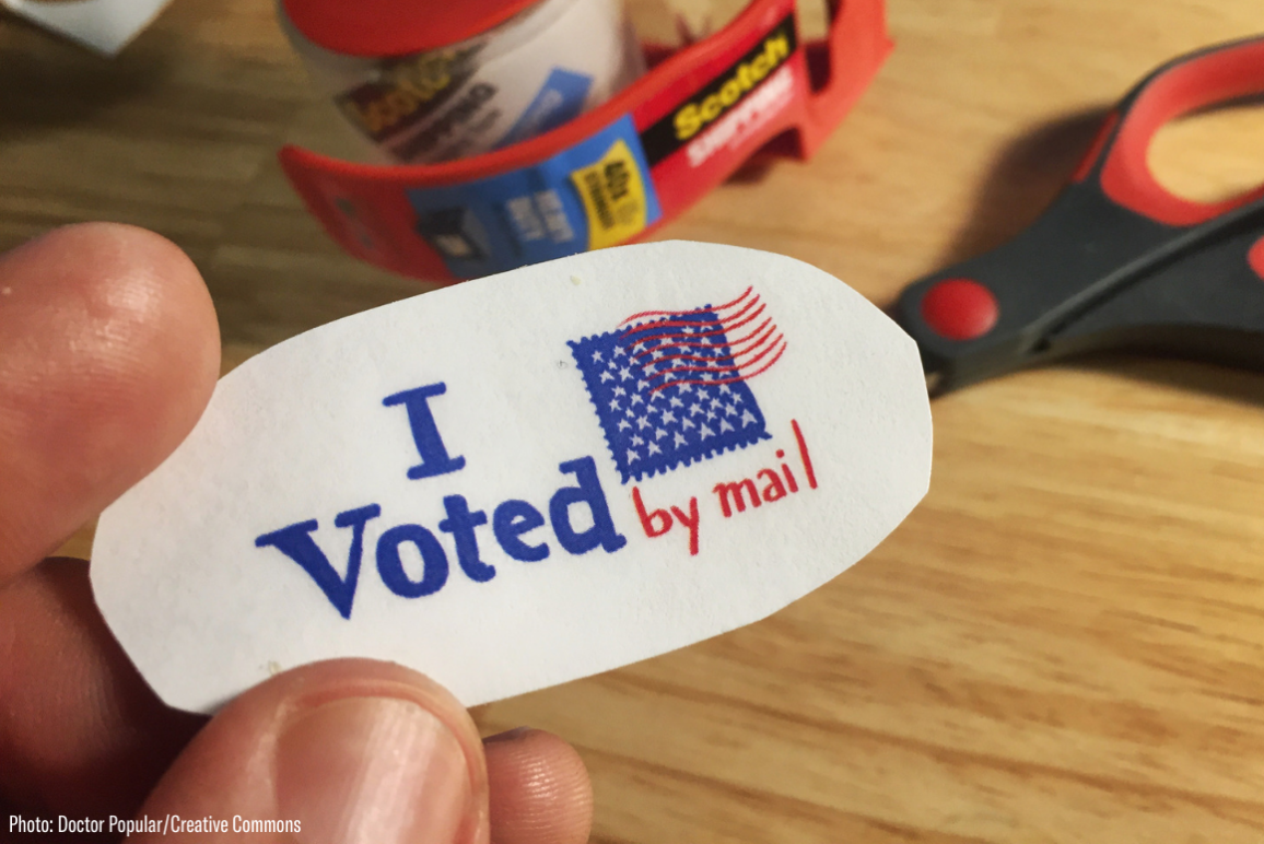 "A hand holding a sticker that says ""I Voted By Mail"""
