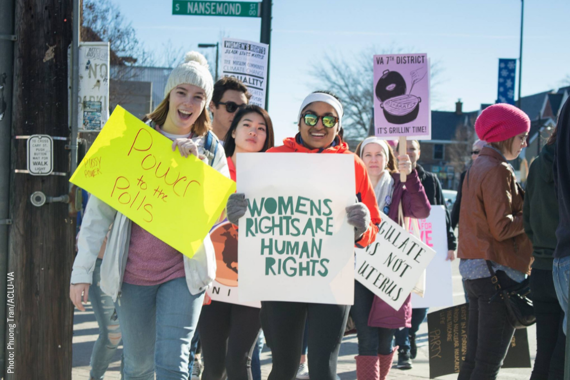 "picture from the 2018 Women's March in Richmond, of a dark-skinned woman holding a sign that said ""women's rights are human rights"" and another white woman holding a sign that said ""Power to the Polls"""