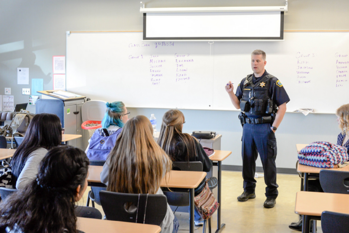 A school resource officer speaking to a class a female students