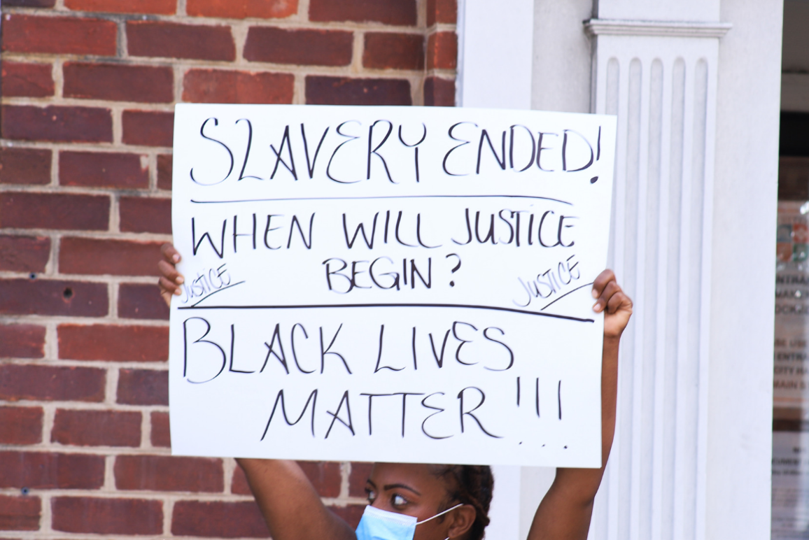 """Black woman holding a protest sign that says """"slavery ended, when will justice begin? Black lives matter!!!{"""""""