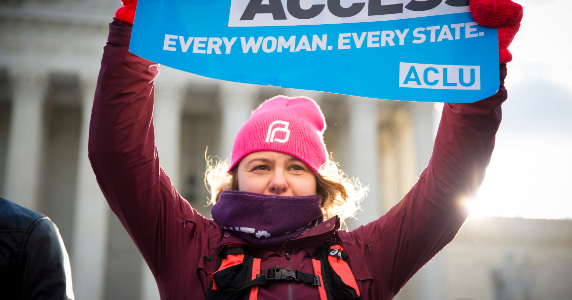 "A white woman holding an ACLU branded sign that said ""Abortion Access. Every Woman. Every State."""
