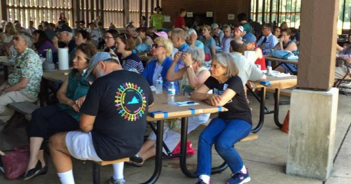 People at picnic tables listening to speaker at crabfest