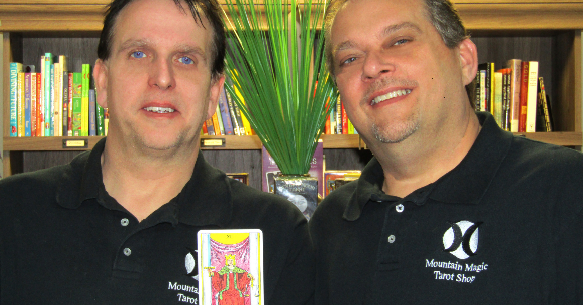 "Picture of our client Mark Mullins and his husband, Jerome, holding a Tarot card that says ""Justice"""